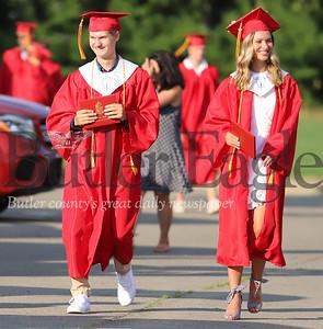 Bryce Kopchak and Carlie Kreutzer walk through the North Catholic High School parking lot during graduation ceremonies Friday. Seb Foltz/Butler Eagle 0724/20