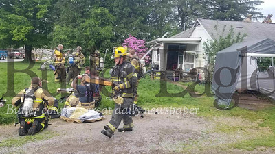 Firefighters rest after battling a house fire at about 10:10 a.m. Tuesday on East Mercer Street in Harrisville. Jim Smith/Butler Eagle  June 2, 2020