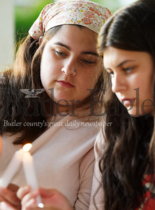 """Harold Aughton/Butler Eagle: Jada Mason, 19, of Butler lights a candle with her sister Natalie, 16, during a memorial service at Rotary Park honoring the memory of George Floyd. The event was organized by Butler resident Jamie Lee. """"I wanted to really bring the community together as a community,"""" said Lee."""