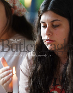 Harold Aughton/Butler Eagle: Natalie Mason, 16, of Butler protects her candle from the wind during a service honoring the memory of George Floyd in Rotary Park, Tuesday, June 2, 2020.