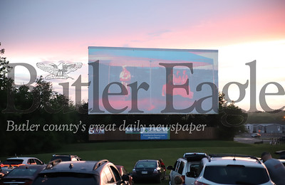 Friends and famliy watch Slippery Rock High School graduates walk on the big screen during ceremonies at the Starlight Drive In. Seb Foltz/Butler Eagle