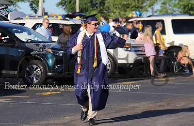 Anthony Gatto waves to family and friends as he walks through the parking lot of Mars High School during the school's graduation cermony Friday. With social distancing guidlines, the school district held graduation in the high school parking lot with families parked in every other spot. Students recieved their diploma, posed for pictures and then walked through the parking lot to cheers and congratulations. Seb Foltz/Butler Eagle 06/12/20