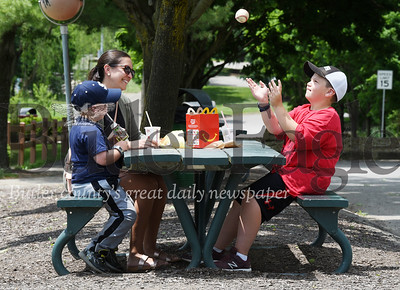 Harold Aughton/Butler Eagle: Oliver Umpleby, 10, of Cranberry Twp. tosses a baseball that he found in the creek while having lunch with his brother, Griffin, 5, and babby sitter, Jessica Bickert Monday, June 15 in the Cranberry Twp. Community Park.