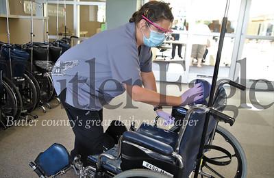 Butler Memorial Hospital patient escort Brenda Lauer cleans a wheelchair at the hospital's enterance Thursday. Seb Foltz/Butler Eagle 06/18/20