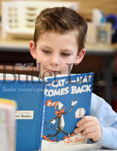 Harold Aughton/Butler Eagle: Butler Catholic first grader, Scout Bicker, reads Dr. Seuess' The Cat in the Hat Comes Back during National Read Across America day in Mr. Brian Herlihy's class Monday, March 2, 2020.