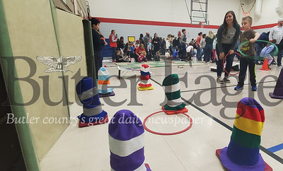 Logan Fetsko, kindergarten, tosses large hoops at cones at the Dr. Suess celebration Wednesday night at Slippery Rock Area Elementary School. Also pictured is Volunteer Brooke Moore, junior at Slippery Rock University. Nathan Bottiger/ Butler Eagle
