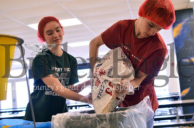 Mars Area High School ninth graders Meredith Wawrzynski, left, and Sawyer Garcia pour rice from a bag to sort it into prepackaged meals. Tanner Cole/Butler Eagle