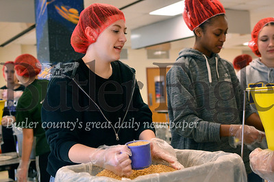 Junior Ashley Ward, left, and junior Alek Johnson package dry meals to be shipped overseas to developing countries. Tanner Cole/Butler Eagle