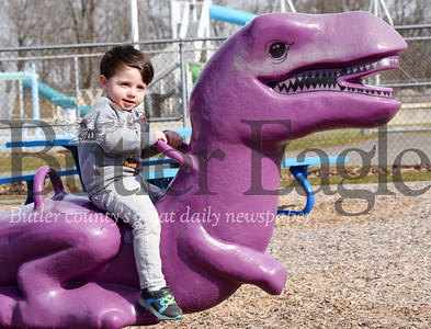 Harold Aughton/Butler Eagle: Reece Mueller, 2. of Parker takes a ride on the purple T-rex at the the Alameda Playground with his mother, Megan, Monday, March 9, 2020.