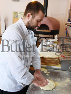 Harold Aughton/Butler Eagle: Chef Spencer McKivigan at the Mac's Brick Oven Pizza begins the process of making a pizza by spreading out the dough.