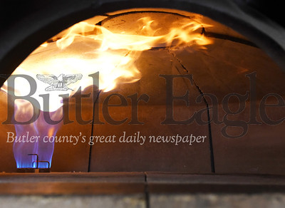 Harold Aughton/Butler Eagle: Gas fire flames heat the brick oven to a cooking temp of about 750 degree s at Chef Spencer McKivigan, Mac's Brick Oven Pizza.
