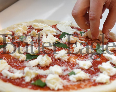 Harold Aughton/Butler Eagle: Chef Spencer McKivigan at the Mac's Brick Oven Pizza places mozzarella cheese on a pizza.
