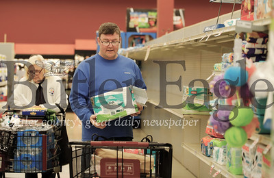David Friel of Butler grabs some rolls of toilet paper off the shelf of the Morraine Point Plaza Giant Eagle Friday. While  the store was well stocked in most departments, customers Friday were taking certain items, such as toilet paper, off the shelves almost as fast as they were being restocked. One Giant Eagle official said there was a direct correlation between items being sold and items recommended for puchase buy national and local news media. Seb Foltz/Butler Eagle