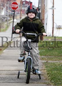 Harold Aughton/Butler Eagle: Julian Shumaker, 5, rides his bike along West Wayne Street Wednesday, March 18, 2020.