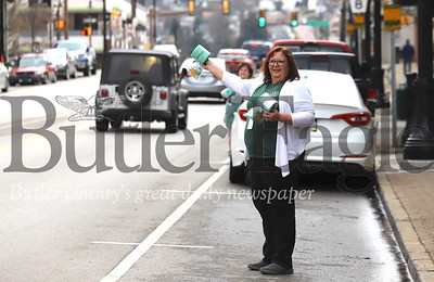 Allison Fischer from Butler's Center for Community Resources hands out free rolls of toilet paper outside of the center's office on Main Street in Butler Thursday. Seeing the shortage and to promote that their office remains open to assist the community, CCR organizers procured select items to hand out along with contact information for the rescource center. The center coordinates connections to services related to mental health, aging, intellectual disabilities, substance abuse and other human service needs in the community. Seb Foltz/Butler Eagle