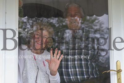 Jim and Cooky Diamond wave from behind the glass front door of their Meridian home Thursday. The Diamonds' daughter Teresa arranged to have a birthday sign celebrating Cooky's 85th birthday setup to greet her Thursday morning. The Diamonds have been self-isolating  and taking other precautions due to the COVID-19 pandemic, including having Teresa  deliver their groceries. Seb Foltz/Butler Eagle