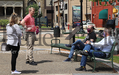 """Butler County Chamber of Commerce exectutive director Jordan Grady (center) takes advantage of sunny skies and the county's """"yellow"""" designation to chat with Audrianna Bly (left), Mike Robb (right) and Chris Lunn in Diamond Park Friday. Seb Foltz/Butler Eagle"""