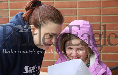 HIS Kids Christian School second grader Claire Baeher looks over her assignment packet from her teacher Mrs. Collins with her mother Courtney Baeher. Seb Foltz/Butler Eagle 05/13/20 (Thursday)