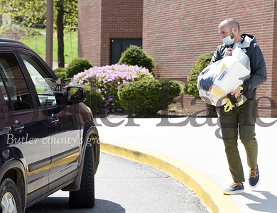 Harold Aughton/Butler Eagle: Mike Stimac, junior high school principal at Karns City, delivered personnel belongings to parents and students during a curbside pickup, Tuesday, May 19, 2020.