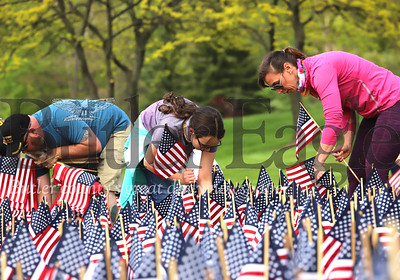 Meghan McGee (center), her mother Sara McGee and volunteers from the Butler County Suicide Prevention Coalition and Mission 22 veterans suicide prevention group place 660 flags on the front lawn of the office building across from Butler RV Center on Route 8 south of Butler. According to Megan Klingensmith of Mission 22, roughly 660 veterans commit suicide each month. Mission 22 offers assistance to veterans in need.  Seb Foltz/Butler