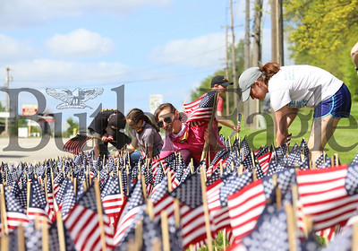 Sara McGee of Penn Township and volunteers from the Butler County Suicide Prevention Coalition and Mission 22 veterans suicide prevention group place 660 flags on the front lawn of the office building across from Butler RV Center on Route 8 south of Butler. According to Megan Klingensmith of Mission 22, roughly 660 veterans commit suicide each month. Mission 22 offers assistance to veterans in need.  Seb Foltz/Butler