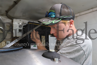 William Thiele of Thiele Dairy Farm in Cabot checks milk level in a holding tank after milking. Like many area farmers Thiele has seen a significant drop in milk sales due to the COVID-19 pandemic. Thiele has been able to mix unused milk in with feed instead of wate. Seb Foltz/Butler Eagle