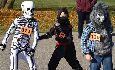 From left, Jack Llewllyn, 8, Hugh Friel, 6, and Jack baumgartner, 7, danced for the judges of the Adams Twp. Halloween Parade Saturday, October 31, 2020. Hundreds of families attended the parade which was led by the Adams Twp. police and fire departments....