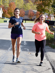 Slippery Rock University students Annie N., left, a junior socialogy major, and friend, Shelby Gluth, a senior public health major, take a jog between classes Thursday, November 5, 2020.