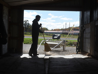 Aaron Johnston sweeps out his barn at the Butler Farm Show. Harold Aughton/Butler Eagle.