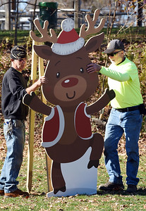 Jim Humes, left, and co-worker Rob Mitchell,of the Butler County Parks & Recreation, erect a cutout of Rudolph the Red Nose Reindeer in Alameda Park Wednesday, Nov. 4, 2020. Fifteen displays have been set up throughout the park in preparation for Santa's Workshop, a drive-through event, being held from 6 - 8 pm, Friday, Nov. 20, 2020. The cost is $7.00 per child. Each child will receive a gift from Santa as well as a craft and candy cane along the route. Harold Aughton/Butler Eagle
