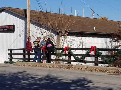 Jim Smith photo. Cheryl Speir (second from left), a Historic Harmony board member, and members of the Seneca Valley High School Key Club, place Christmas decorations on the bridge next to the Harmony Fire District station Sunday.