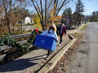 Jim Smith photo. Dylann Volz of Cranberry Township, a 10th grade student at Seneca Valley High School and a member of the school's Key Club, carries a tote of Christmas swags and wreathes while helping to decorate Harmony for the holidays Sunday.