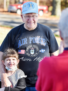 Airforce veteran Al Wilson of Saxonburg poses with his great, granddaughter Rylee Wilson as his wife, Ruth Wilson takes a photograph during the drive-through Veterans Day celebration at His Kids Christian School in Jefferson Twp Tuesday, November 10, 2020. Harold Aughton/Butler Eagle.