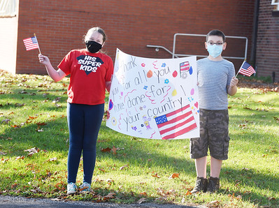 Fifth graders Ariel Lake, left, and Charlie Perfors showed their appreciation to the veterans who attended the drive-through Veterans Day celebration at His Kids Christian School Tuesday, November 10, 2020. About 60 Students in grades pre-school through 6th grade cheered as veterans' related to the staff or students drove around the school's driveway. The students sang God Bless America as well as other patriotic songs for the eight veterans who attended the event. Harold Aughton/Butler Eagle