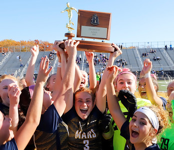 Mars Ellie Coffield raises the WPIAL trophy with teammates Saturday following the Planet's 1-0 win over Plum, earning Mars back-to-back titles. Seb Foltz/Butler Eagle 11/07/20