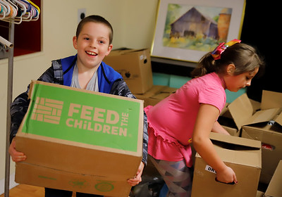 Daniel Meegan, 8, and Maggie Koziar, 8, of Butler help carry out boxes of food dontated to the  Butler Hip Hop and Rap Community's food drive for veterans Friday. Volunteers collected food at the Butler Art Center to be distributed to local veterans. Seb Foltz/Butler Eagle 11/13/20