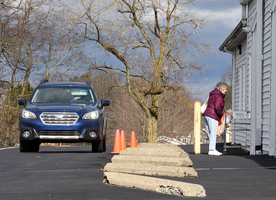 Joyce McConahy of Saxonburg picks up a book at the South Butler Community Library while her longtime friend Cora Biancho waits in the car Tuesday, November 17, 2020. The library has closed its doors to walk-through traffic and reopened its drive-through window due to COVID 19. Harold Aughton/Butler Eagle