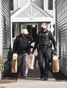 Friends of Saxonburg Police volunteer Bill Hoche, left, and officer Joe Beachem deliver groceries to the residents of The Commons of Saxonburg, Thursday, November 19, 2020.