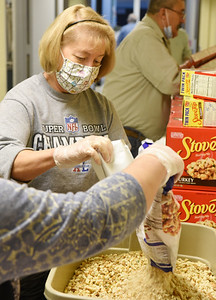 Volunteers Mary Graham, left, and Amanda Brendlinger prepare to make stuffing at St. Michael's parish Wednesday, November 25, 2020. Harold Aughton/Butler Eagle