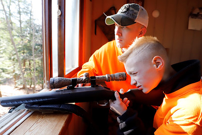 Kyle Osborn,11, and his father Doug look out from the family's tree-house-style hunting blind Saturday on their property near Grove City. Seb Foltz/Butler Eagle 11/28/20