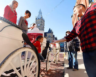EDITORS NOTE: Better as secondary photo. Sean Harcar of Butler offers to help his daughters Aria,6,  down from a horse carriage with his other daughter Sienna, 10, and partner Jamie Sears in Diamond Park Saturday. Carriage rides from Misty Lane Performance Horses were part of Butler Main Street's Small Business Saturday. Seb Foltz/Butler Eagle 11/28/20