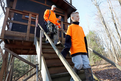Kyle Osborn, 10, his father Doug, sister Maddie, 11, (not pictured) and mom Amber leave the family's tree-house-style hunting blind Saturday to walk back to their house. Doug and Amber take turns hunting with four of their five kids in the elaborate treestand behind their home near Grove City. Seb Foltz/Butler Eagle 11/28/20