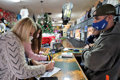 Barb and Anna Blauser of Chicora turn in their Small Business Saturday passports to Branded in Butler co-owner Brendan O'Brien Saturday. Shoppers could get their passport stamped at participating businesses to earn a chance at raffle prizes. Seb Foltz/Butler Eagle 11/28/20
