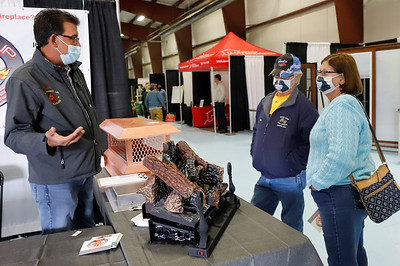 Pat (right) and Joe Green of Butler talk with Dave Anthony of All Fired Up Fire Places at the Butler Home Show Friday. Seb Foltz/Butler Eagle 10/2/20