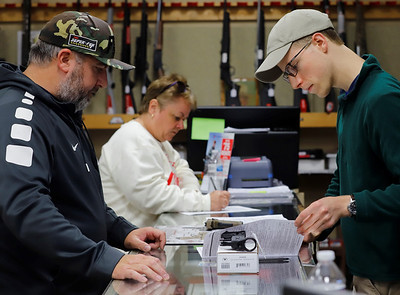 Preston Snyder (right) of Fenelton Firearms looks over Todd Gray(left) of Fenelton's background check forms for a gun part purchase Friday. Seb Foltz/Butler Eagle 10/02/20
