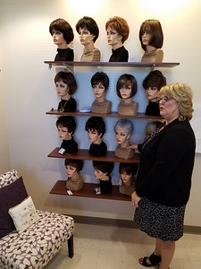 Stacy Meyer shows off some of the wigs available for cancer patients at her hair salon