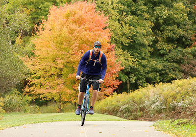 With leaves begining to turn, a cyclist rides the recreation trail on Morraine State Parks North Shore Wednesday. Seb Foltz/Butler Eagle Oct. 7 2020