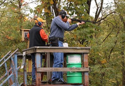 Josh Osche lines up his shot at a clay target with his father Jim Osche of Butler Saturday at the Butler PM Rotary Robin's Home Fundraiser. Seb Foltz/Butler Eagle