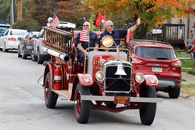 Cranberry Township fire fighters drive the departments antique fire engine during Saturday's Zelienople Library parade. Seb Foltz/Butler Eagle