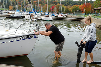 Bill Sanoske helps guide Hailey Vey of Cranberry's sail boat on to its trailer to Saturday at Morraine State Park's Davis Holow Marina. Marina users have to till the end of the month to move thier boats to storage. Seb Foltz/Butler Eagle